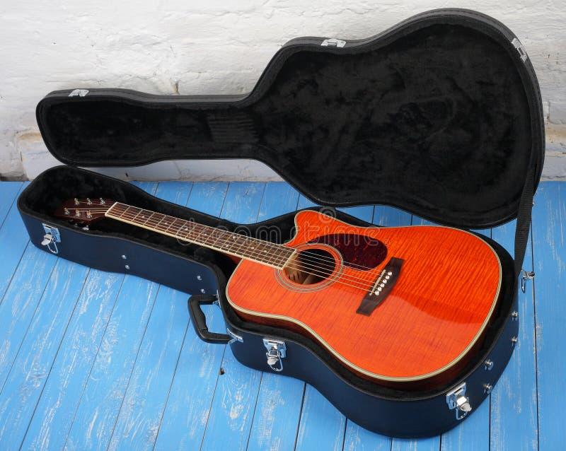 Musikinstrument - orange akustisk gitarr i hårt fall royaltyfri foto
