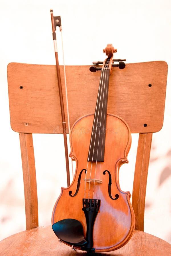 Musikinstrumentsmåbarnfiol med pilbågeställningar på gammal trästol som lutar mot dess baksida Begreppsmusikal royaltyfri bild