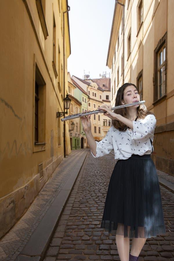 Musikkapacitet Bedöva den eleganta unga damen med tvärflöjtinstrumentet royaltyfria foton