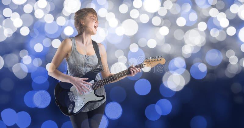 Musikkonstnär som spelar gitarren över bokeh arkivfoton