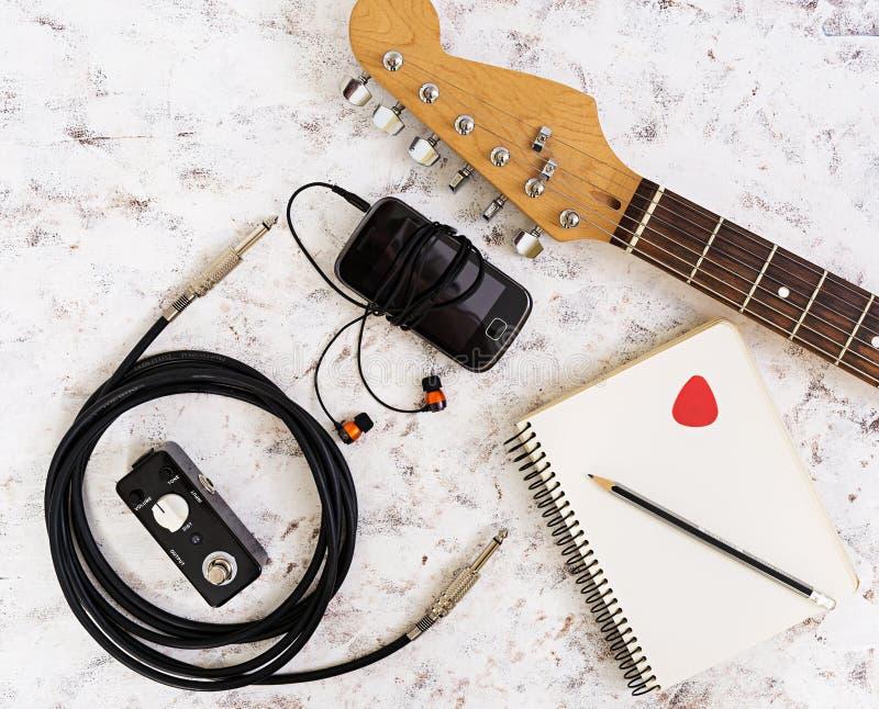 Musikmaterial Gitarr gitarrpedal, headphone, mobiltelefon på vit bakgrund Top besk?dar Lekmanna- l?genhet fotografering för bildbyråer