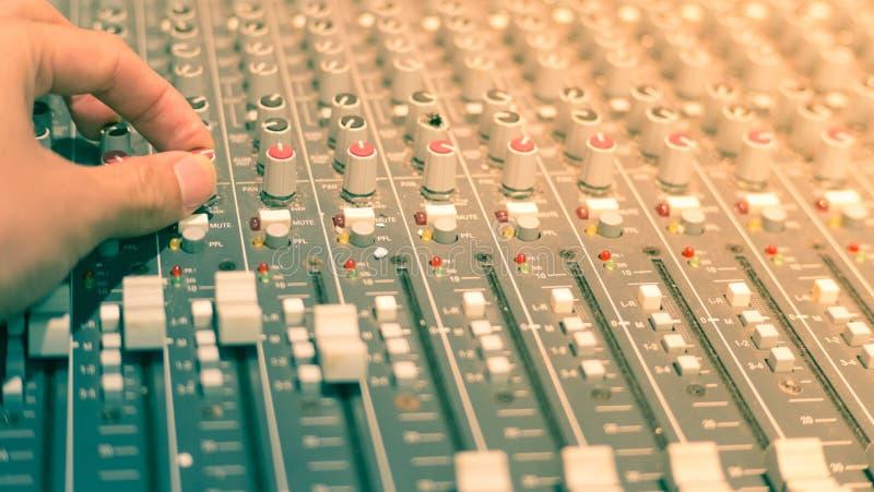 Musikmischer mit der Hand justieren die Griffe stockfoto