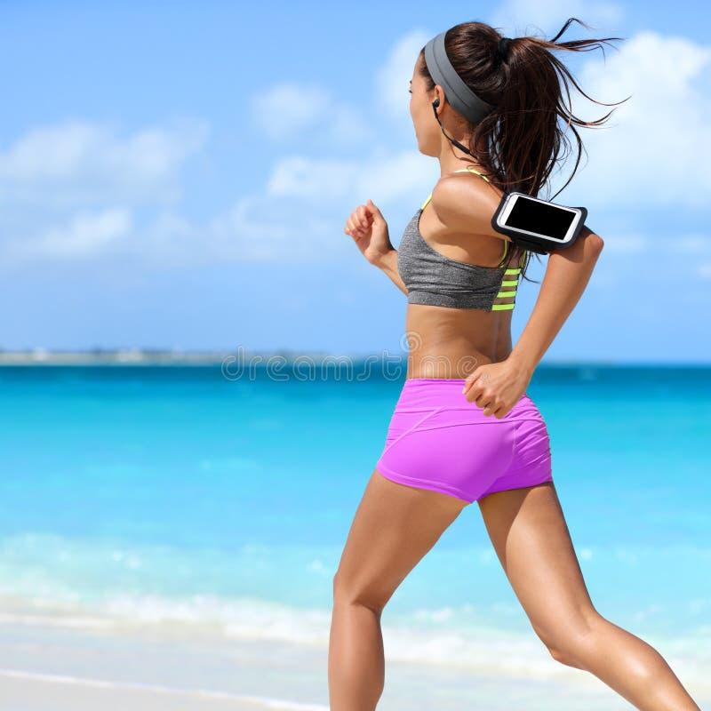 Musikmotivation für laufenden Frauenläufer des Strandes stockfotos