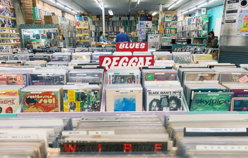 Musikrekordet shoppar inre med kuggar som är fulla av tappningvinylreco royaltyfri bild