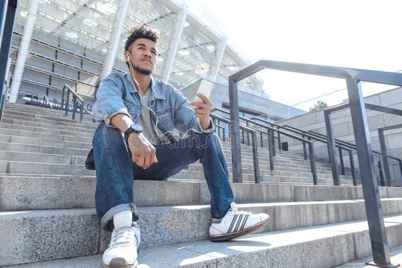 Musikvän Mulattgrabb i hörlurar som sitter på trappa med sikt för musik för smartphone lyssnande eftertänksam nedersta arkivbilder