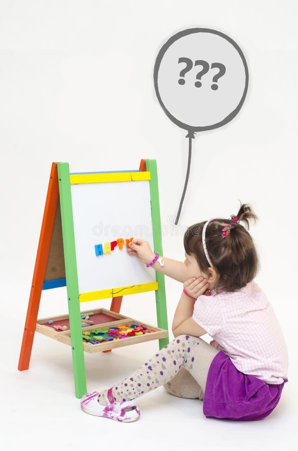 Musingly девушка клеит магнитные письма на интересовать белой доски стоковая фотография