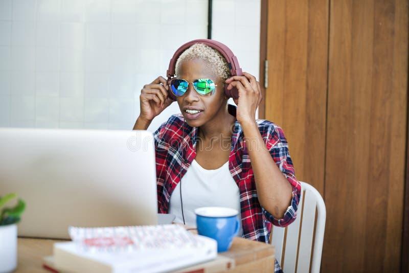Musique africaine d'ordinateur portable de femme coulant la technologie Conce de relaxation photos libres de droits
