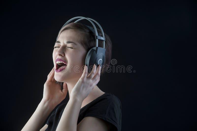 Musique de écoute de belle fille dans les écouteurs et le chant images stock