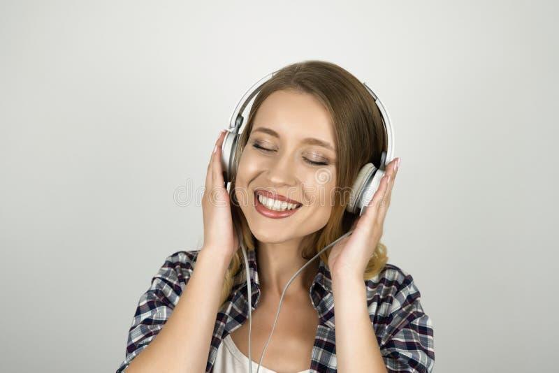 Musique de écoute de belle jeune femme à l'arrière-plan blanc d'isolement de sourire d'écouteurs image libre de droits