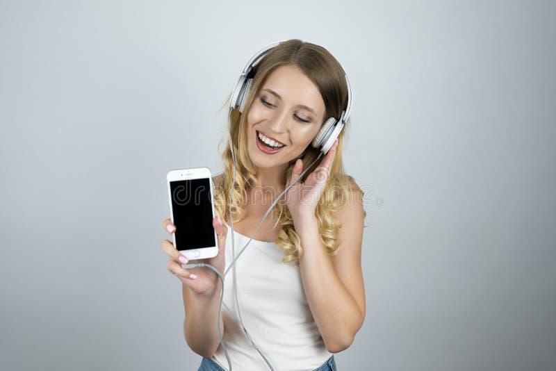 Musique de écoute de belle jeune femme dans des écouteurs tenant le fond blanc d'isolement par smartphone images libres de droits