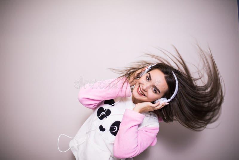 Musique de écoute de belle jeune femme et danse dans le lit d'isolement sur le blanc image stock