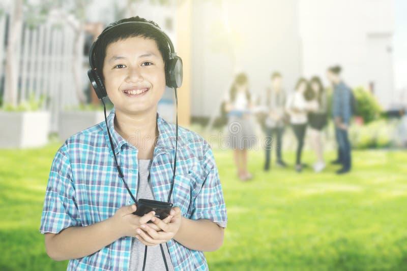 Musique de écoute d'écolier asiatique en parc photo libre de droits
