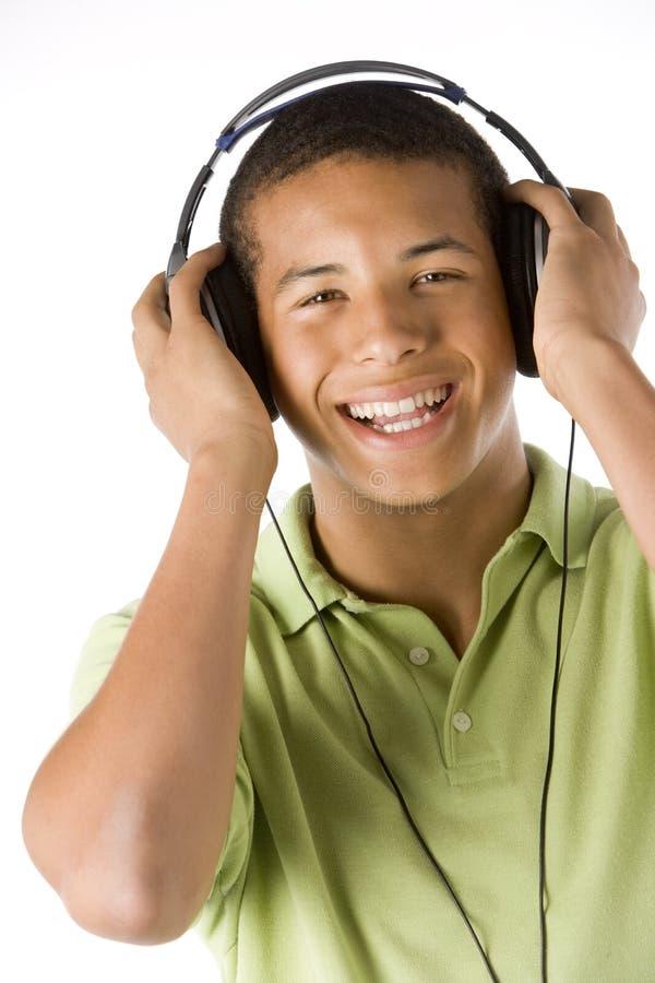 musique de écoute d'écouteurs de garçon d'adolescent à images stock