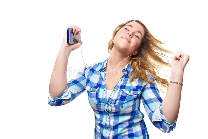 Musique de écoute d'adolescent blond avec le smartphone photos libres de droits