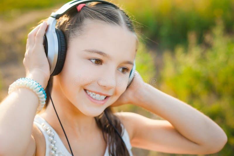 Musique de écoute d'enfant mignon avec des écouteurs et le sourire images stock