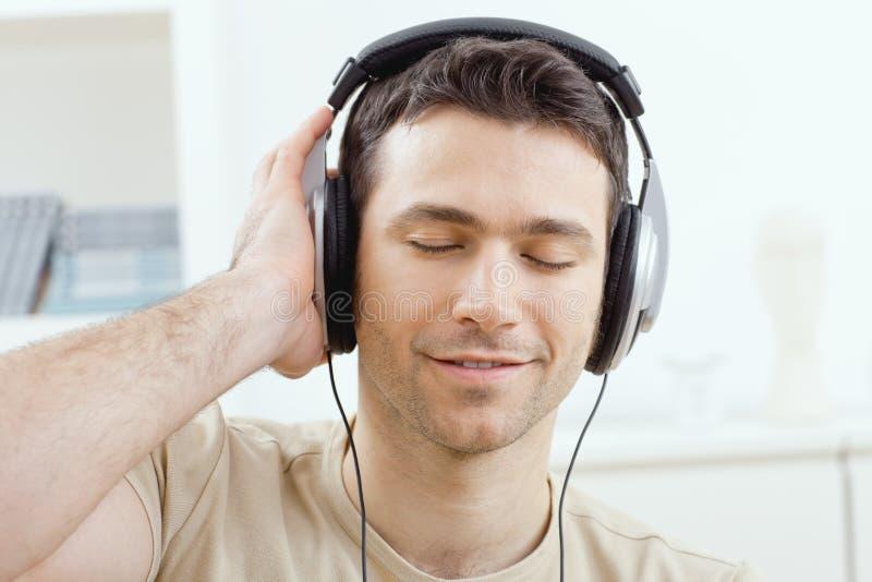 musique de écoute d'homme d'écouteurs image libre de droits