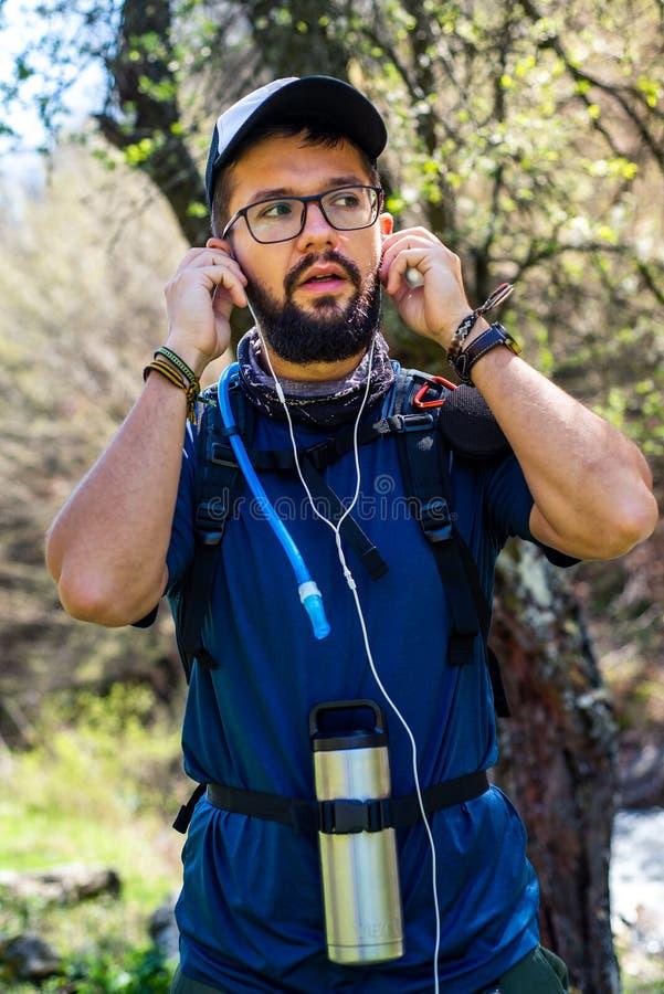 Musique de écoute d'homme gai en voyage de hausse photographie stock