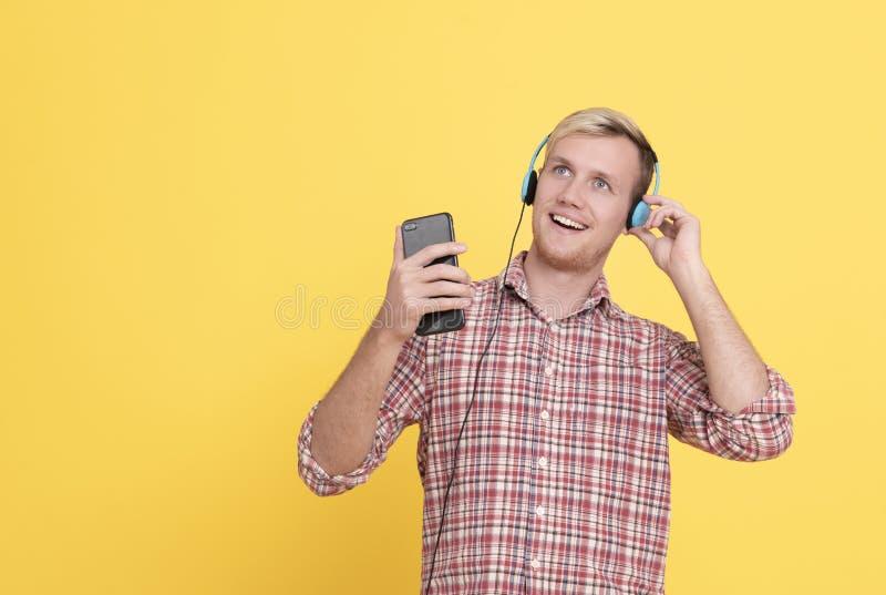 Musique de écoute d'homme de portrait dans des écouteurs et danse au-dessus du fond jaune image stock