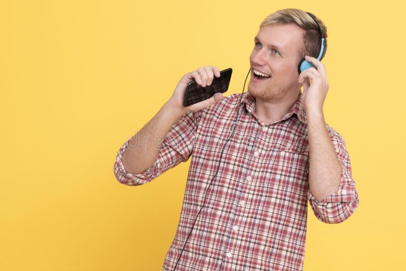 Musique de écoute d'homme de portrait dans des écouteurs et danse au-dessus du fond jaune photos stock