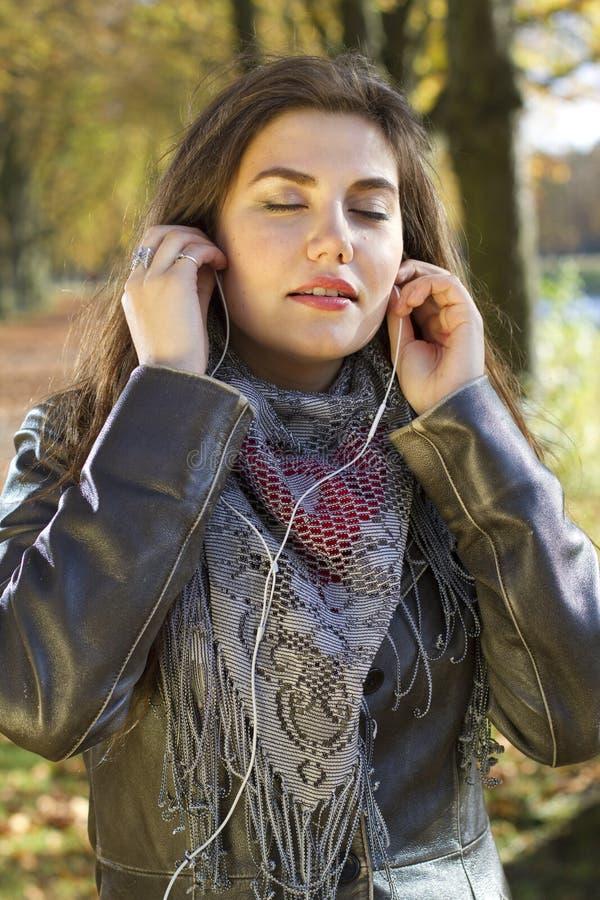 Musique de écoute de femme en stationnement photographie stock