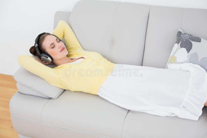 Musique de écoute de femme par des écouteurs sur le sofa photographie stock libre de droits