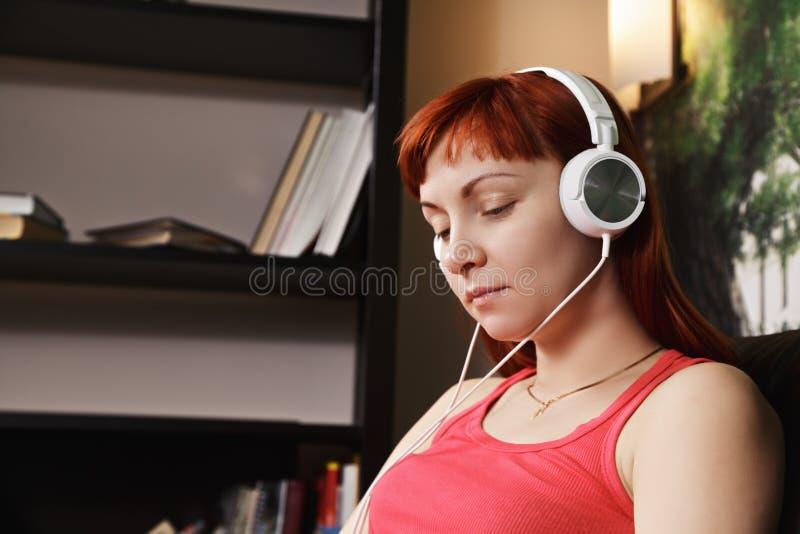 Musique de écoute de femme rousse image libre de droits