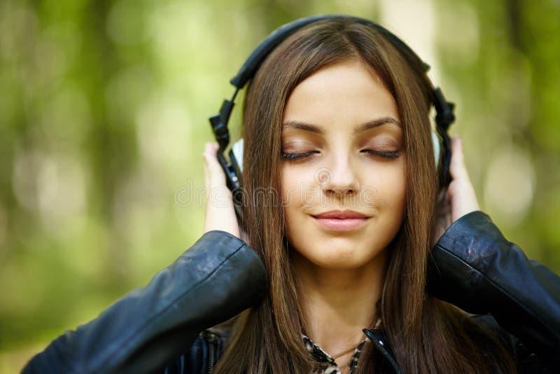 Musique de écoute de fille extérieure photos libres de droits