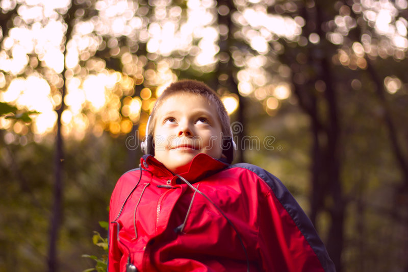 Musique de écoute de garçon dans la forêt photos stock