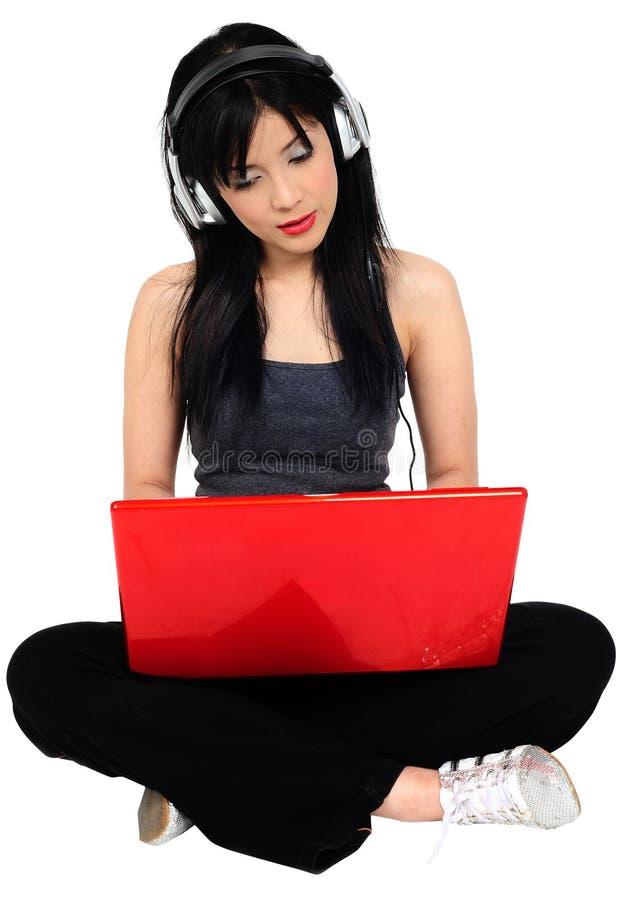 Musique de écoute de jeune femme asiatique du calcul images stock