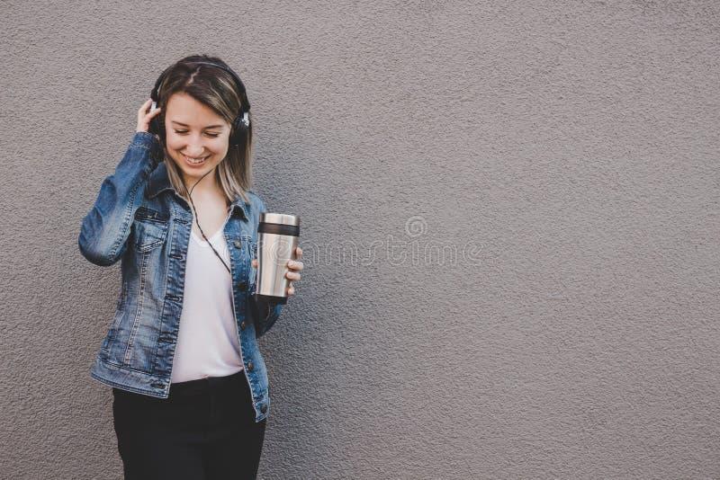 Musique de écoute de jeune femme attirante et café potable Fond gris, l'espace de copie photo stock