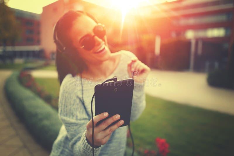 Musique de écoute de jeune femme par le comprimé et les écouteurs dans le coucher du soleil images libres de droits