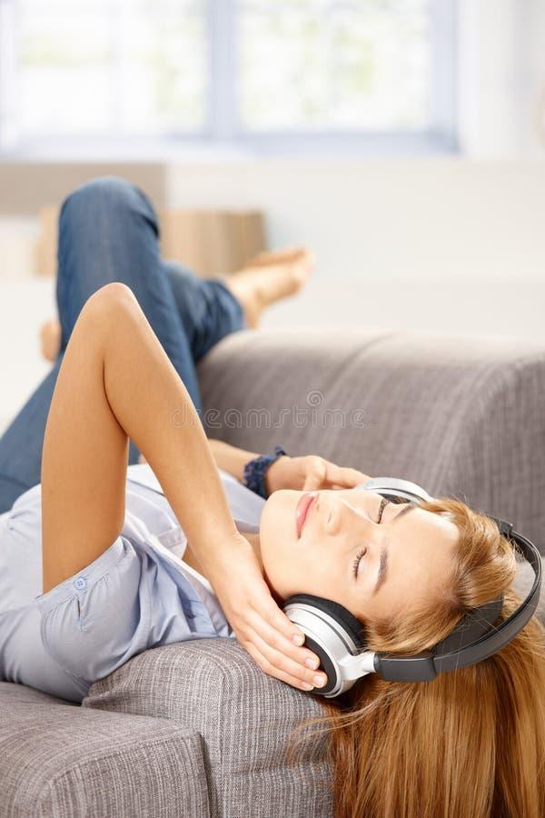 Musique de écoute de jeune femme s'étendant sur le sofa photos libres de droits