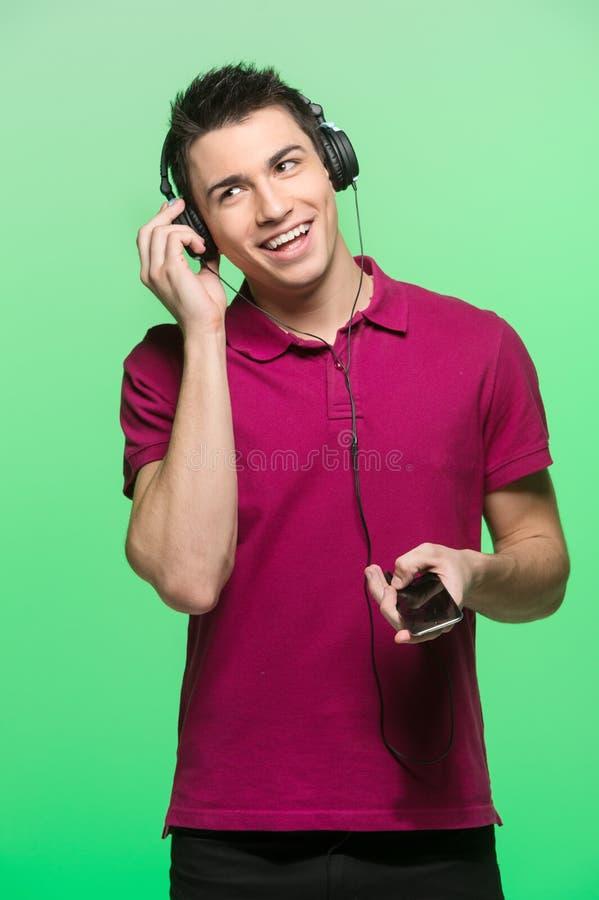 Musique de écoute de jeune homme attirant images libres de droits