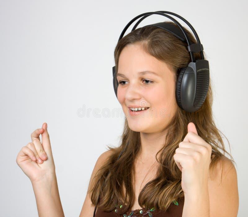 Musique de écoute de jeune jolie fille avec des écouteurs photos stock