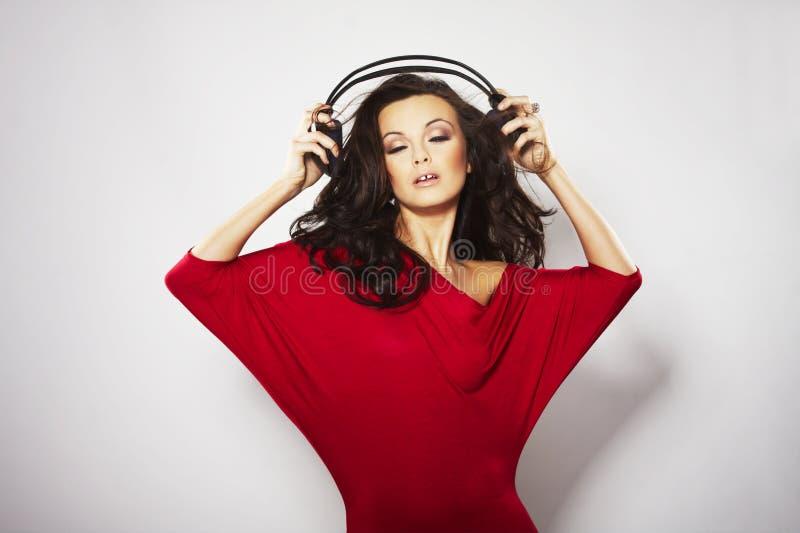Musique de écoute de jeunes beaux femmes heureux image stock