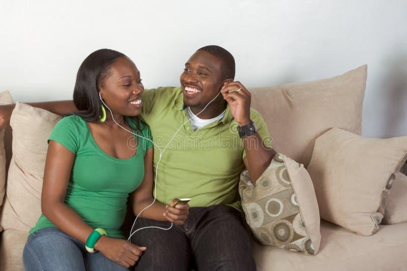 Musique de écoute de jeunes couples noirs ethniques heureux photo stock