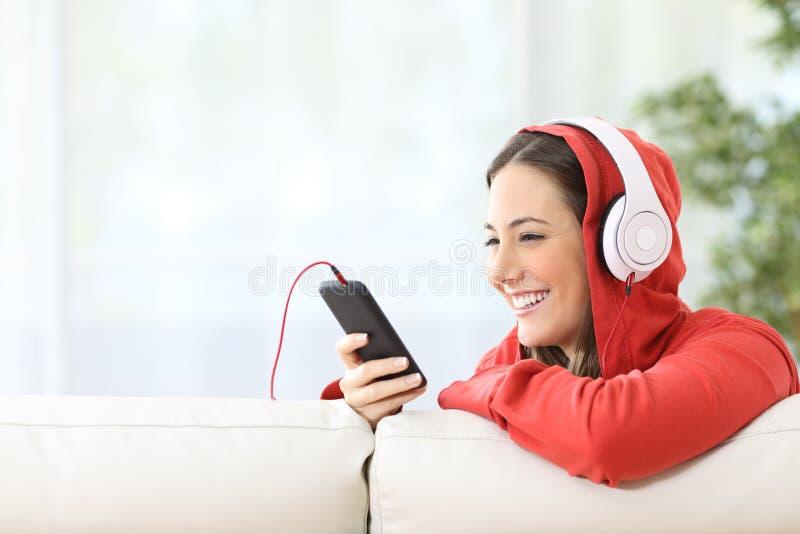 Musique de écoute de l'adolescence heureuse de téléphone photographie stock libre de droits