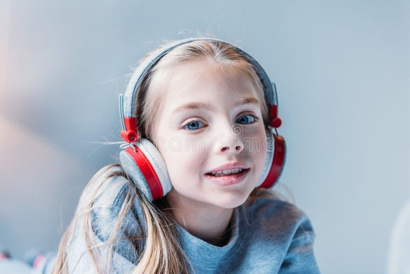 Musique de écoute de petite fille dans des écouteurs et regarder l'appareil-photo photographie stock libre de droits
