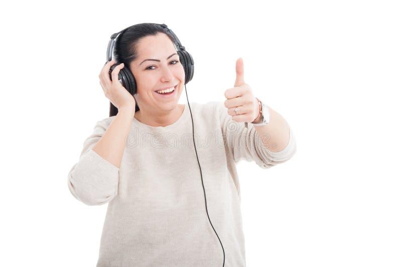 Musique de écoute femelle attrayante sur des écouteurs image stock