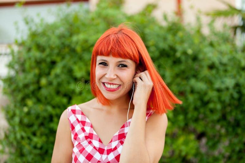 Musique de écoute de femme d'une chevelure rouge décontractée image stock
