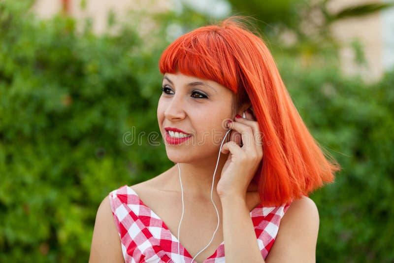 Musique de écoute de femme d'une chevelure rouge décontractée photographie stock