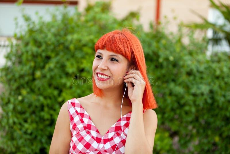 Musique de écoute de femme d'une chevelure rouge décontractée images libres de droits