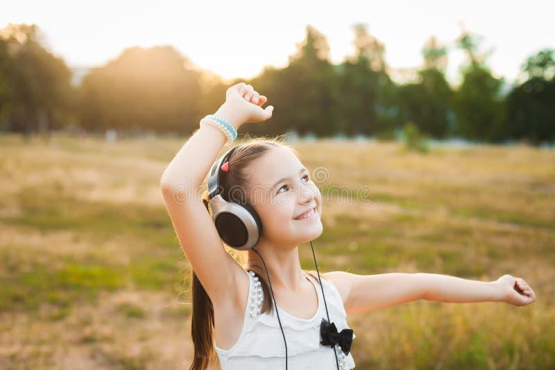 Musique de écoute de fille joyeuse et danse dans le domaine image stock