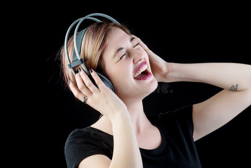 Musique de écoute de fille mignonne dans les écouteurs et le chant images stock