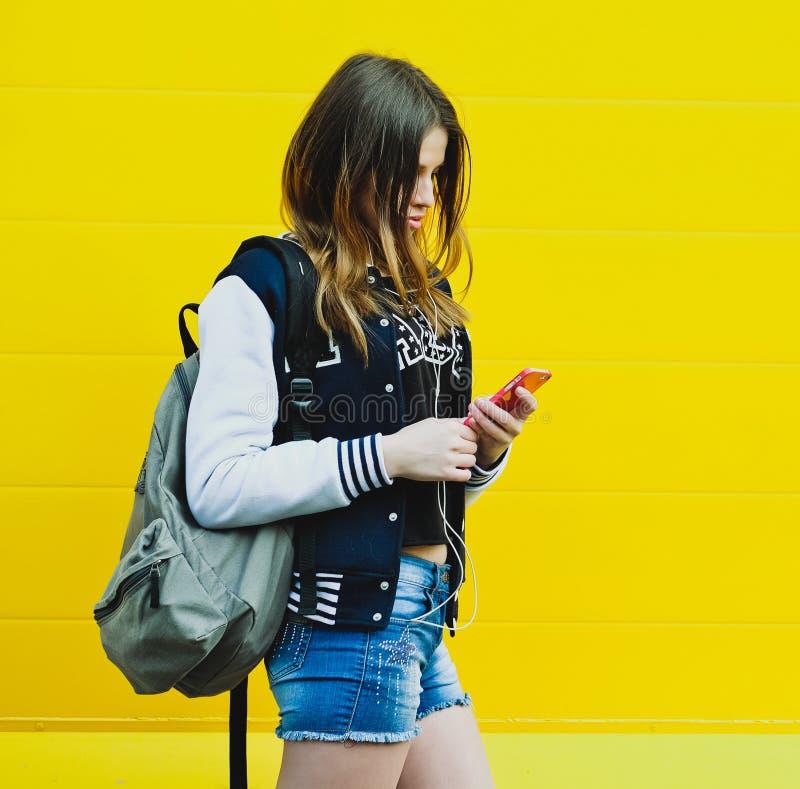 Musique de écoute heureuse de jeune fille dans des écouteurs photos stock