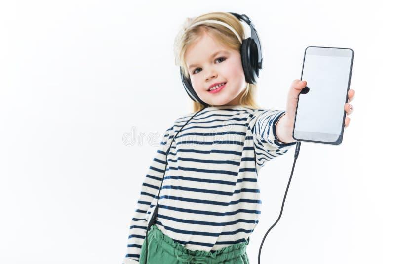 musique de écoute heureuse de petit enfant avec les écouteurs et le smartphone de représentation photo stock