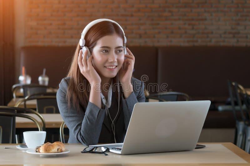 Musique de écoute de jeune belle femme d'affaires asiatique en café images libres de droits