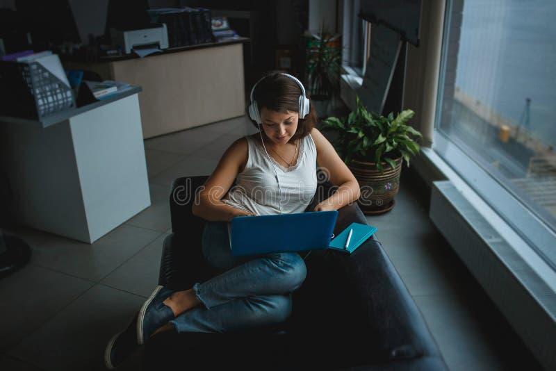 Musique de écoute de jeune femme dans des écouteurs et travailler sur l'ordinateur portable sur le sofa dans le bureau Récréation image libre de droits