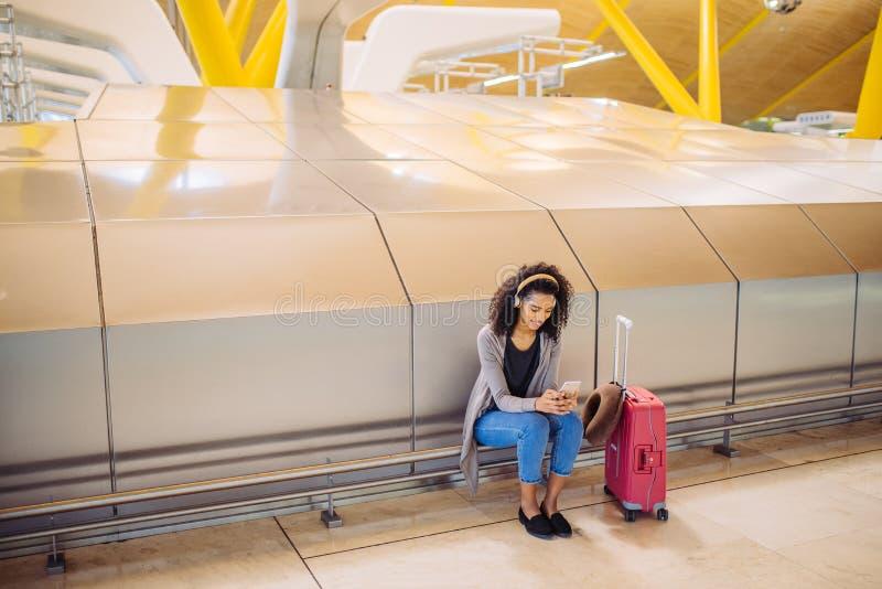 Musique de écoute de jeune femme heureuse avec des écouteurs et le pho mobile photographie stock