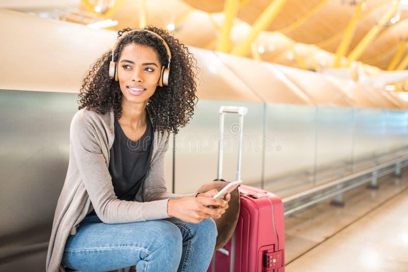 Musique de écoute de jeune femme heureuse avec des écouteurs et le pho mobile images stock